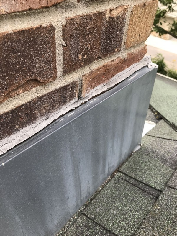 Flashing on chimney has not been installed properly creating the potential for water leakage into the attic.