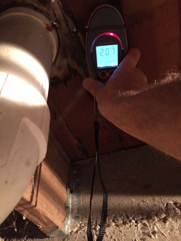 Moisture meter indicating leak under first floor toilet.