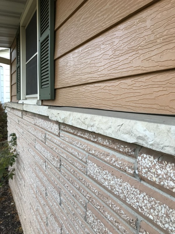 Transition from siding to brick has no flashing.  Stone cap is loose.  Potential source of water penetration.
